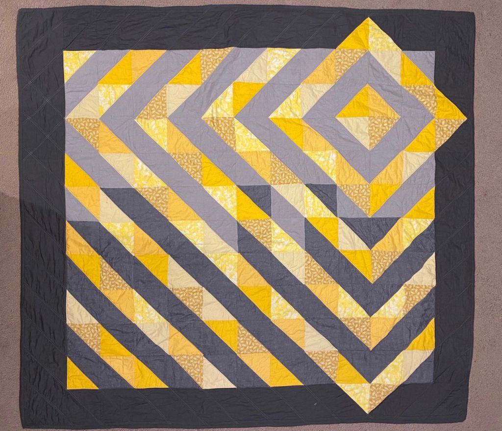 Photo of yellow and grey coloured quilt.