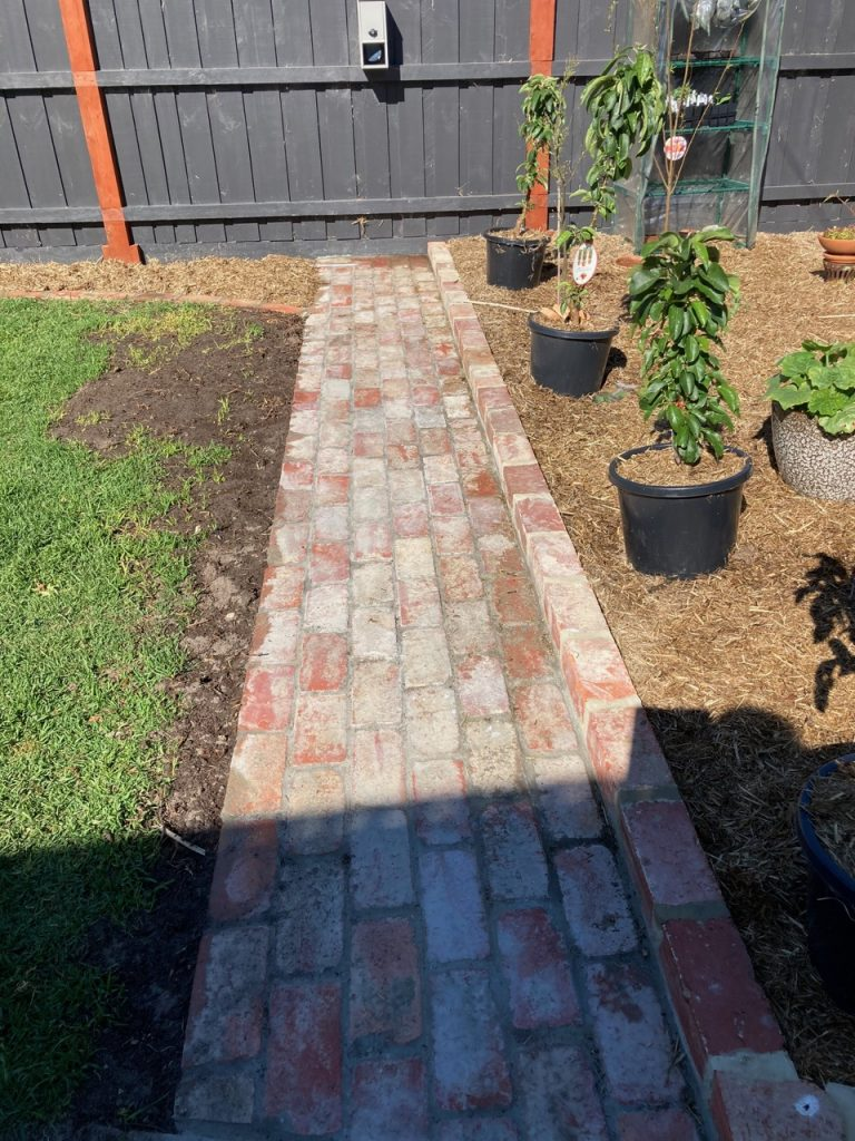 Brick path to the letterbox, next to the 'Orchard.'