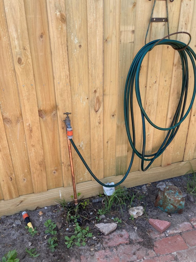 Hose hanging up on the brand-new fence.