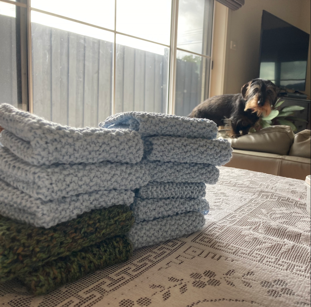 Washcloths piled on a table, with Scout looking on.